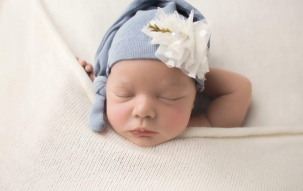 Newborn photography of baby girl in blue sleepy hat tucked in to blankets sleeping