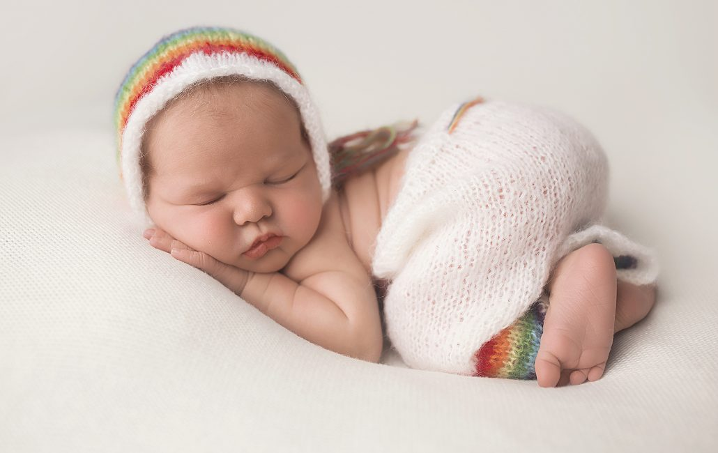 Newborn baby girl in rainbow bonnet and rainbow pants